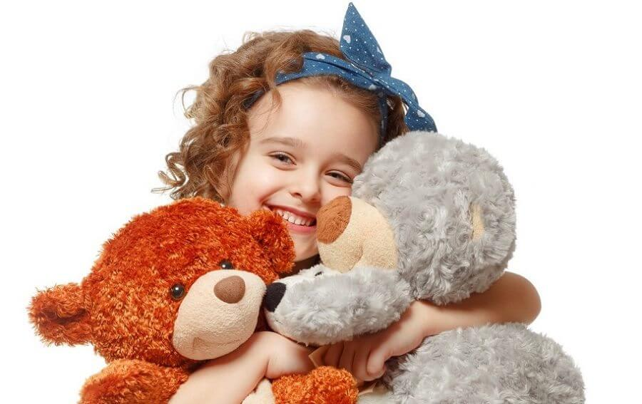 Little girl holding a teddy bear. Isolated on white background